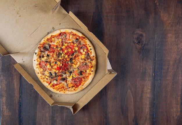 Pizza en una caja de pizza sobre un fondo oscuro de la madera. aplanada Foto gratis