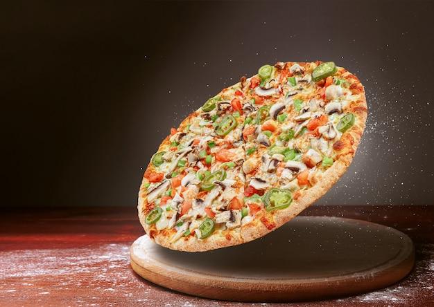 Pizza clásica sobre una superficie de mesa de madera oscura y una dispersión de harina. concepto de menú de restaurante de pizza Foto Premium