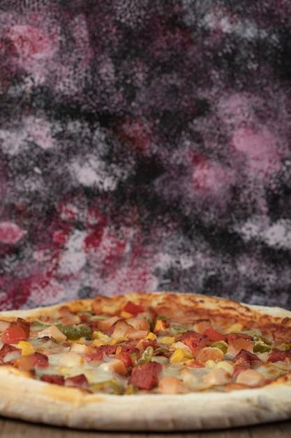 Pizza cocida de ingredientes mixtos con rodajas de pepperoni. Foto gratis