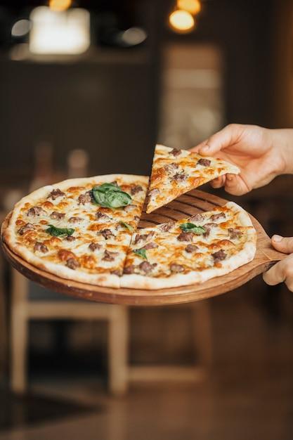 Pizza de ingredientes mixtos en una tabla de madera, tomando una rebanada Foto gratis
