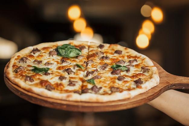 Pizza de ingredientes mixtos en una tabla de madera Foto gratis