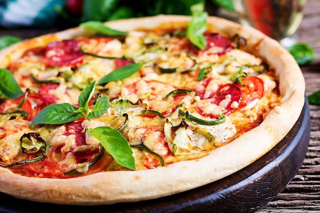 Pizza italiana con pollo, salami, calabacín, tomates y hierbas. Foto gratis