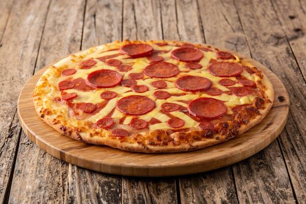 Pizza de pepperoni italiana en mesa de madera Foto Premium