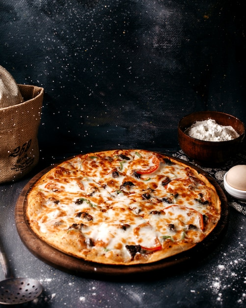 Pizza con queso en la superficie de madera marrón en la superficie brillante Foto gratis