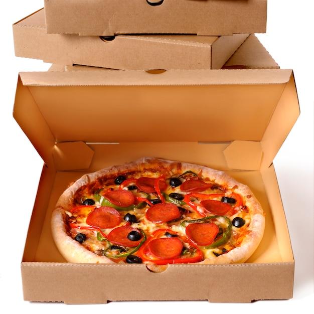 Pizza recién horneada con pila de cajas de entrega Foto gratis