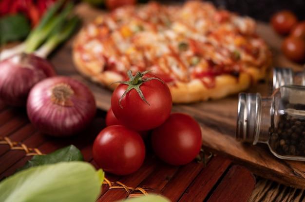 Pizza con salchicha, maíz, frijoles, camarones y tocino en una placa de madera Foto gratis