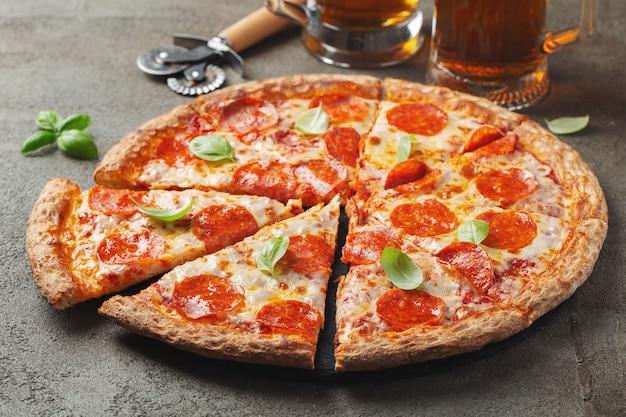Pizza de salchichones sabrosa con albahaca y vidrio de cerveza en fondo concreto marrón. Foto Premium