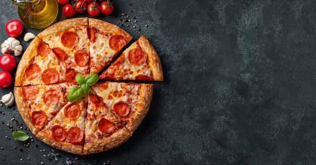 Pizza de salchichones sabrosa en un fondo concreto negro. Foto Premium