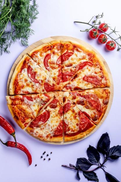 Pizza de tomates, hierbas y pimiento rojo Foto gratis