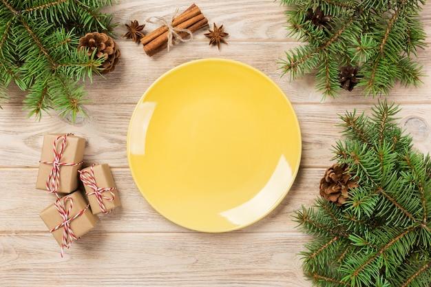Placa mate amarilla vacía en madera. con decoración navideña, plato redondo. año nuevo Foto Premium