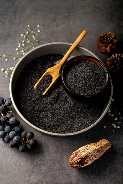 Placa metálica gris llena de semillas de amapola y uvas sobre un fondo gris Foto gratis