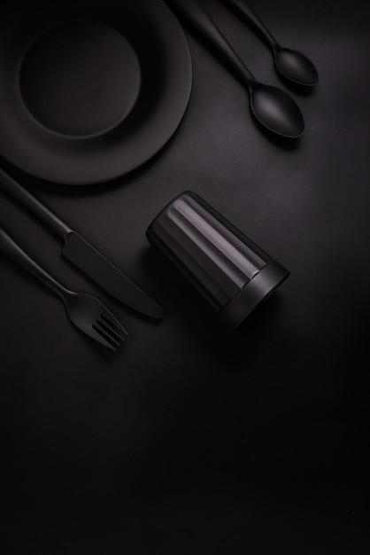 Placa negra, cristal negro y cubiertos negros sobre un fondo negro, vista superior Foto Premium