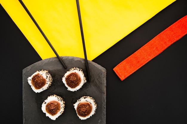 Placa de piedra negra con rollos de sushi sobre un fondo negro Foto gratis