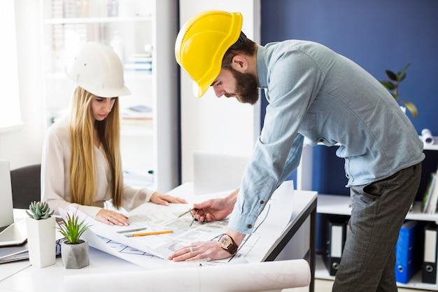 Plan de dibujo de hombre ingeniero en impresión azul con equipo de arquitecto