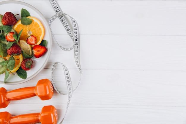 Plan de dieta, menú o programa, cinta métrica, agua, pesas y comida dietética de frutas frescas en blanco Foto Premium