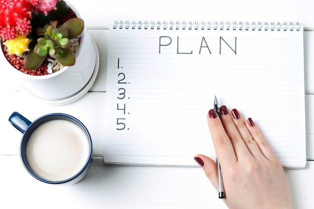Plan de inscripción en el bloc de notas, primer plano, vista superior, concepto de planificación, establecimiento de objetivos Foto Premium