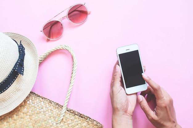 Plana creativa de la colección de verano con mano de mujer usando teléfono inteligente en el fondo de color Foto Premium