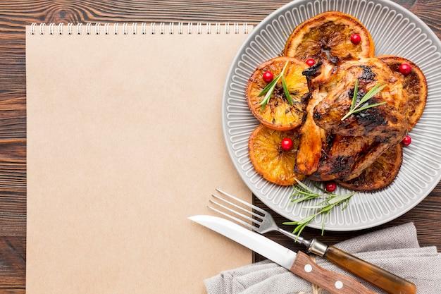 Plana laicos pollo al horno y rodajas de naranja en un plato con cubiertos y bloc de notas en blanco Foto gratis