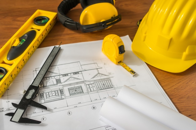 17f5b5c03 Los planes de construcción con casco amarillo y herramientas de ...