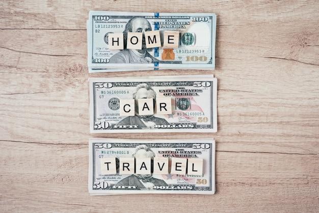 Planificación de presupuesto y concepto de riqueza. palabras coche, casa y viaje en billetes de un dólar, vista superior Foto Premium