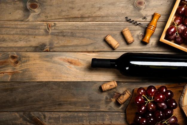 Plano de una botella de vino rodeada de corchos y uvas rojas. Foto gratis