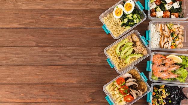 Plano de cazuelas de plástico con comidas y espacio de copia Foto gratis
