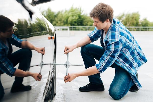 Plano completo del hombre cambiando neumáticos Foto gratis