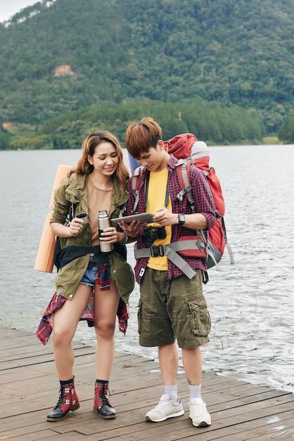 Plano completo de una joven pareja asiática con mochilas de pie en el muelle y planeando su ruta en la tableta Foto gratis