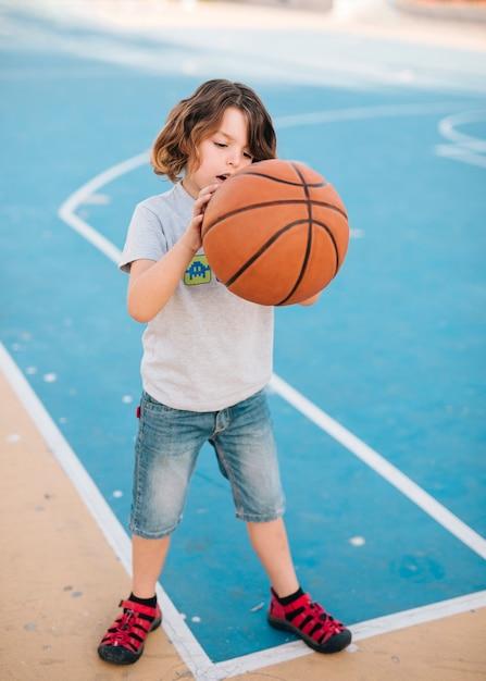 Plano completo del niño jugando baloncesto Foto gratis