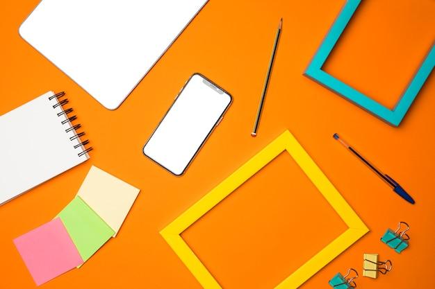Plano concepto de escritorio con fondo naranja Foto gratis