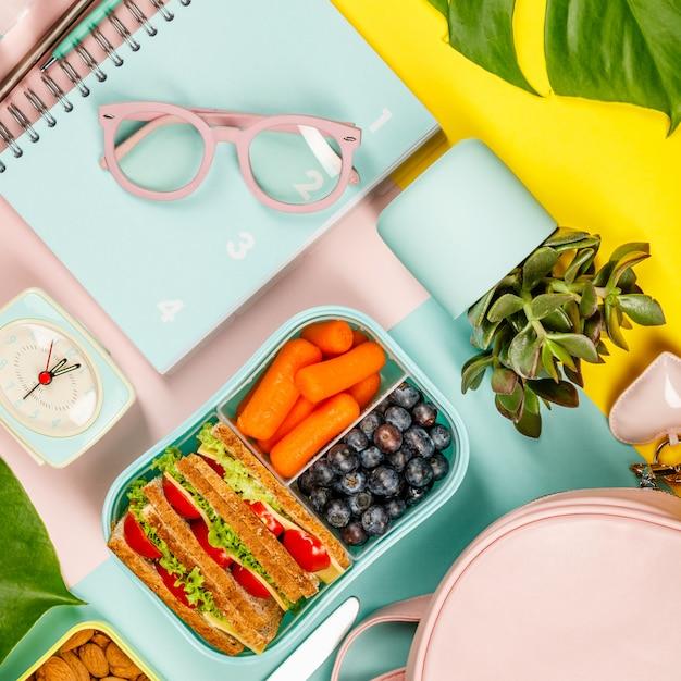 Plano creativo con almuerzo saludable y útiles de oficina. Foto Premium