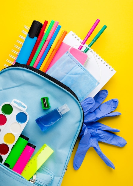 Plano de elementos esenciales de la escuela con guantes y mochila Foto gratis