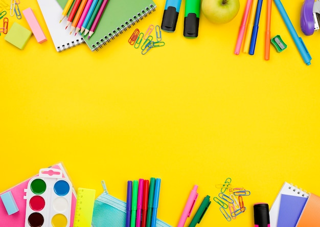 Plano de elementos esenciales de la escuela con lápices y acuarelas Foto gratis