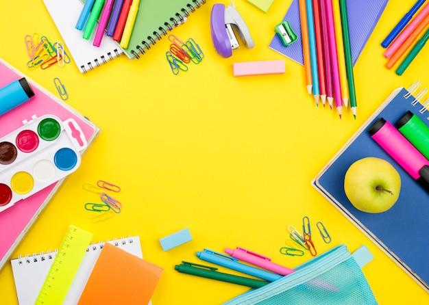 Plano de elementos esenciales de la escuela con lápices de colores. Foto gratis