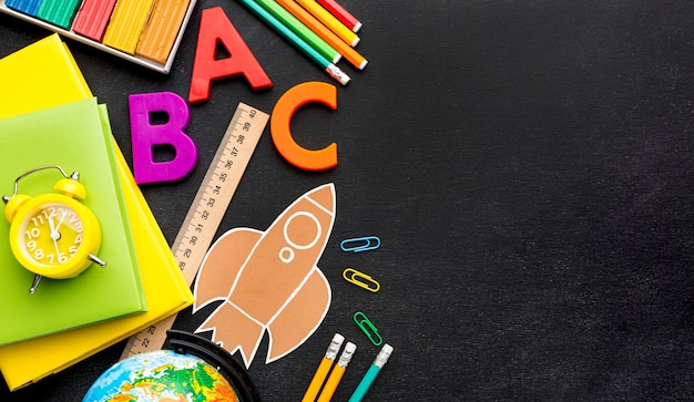 Plano de elementos esenciales de la escuela con libros y espacio de copia Foto gratis
