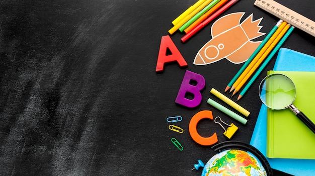 Plano de elementos esenciales de la escuela con lupa y globo Foto gratis