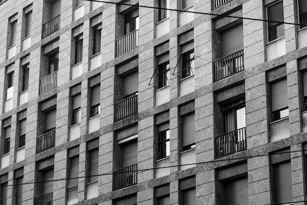 Plano en escala de grises de un edificio largo con ventanas y balcones Foto gratis