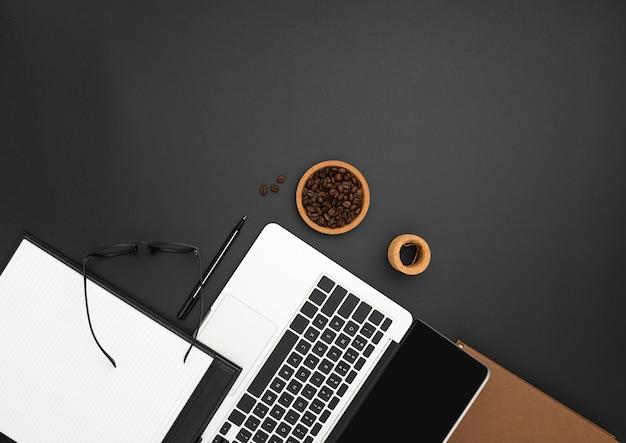Plano de estación de trabajo con computadora portátil y granos de café Foto gratis