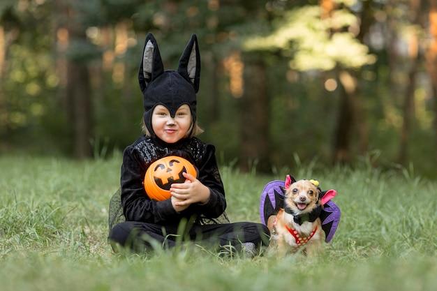 Plano general de niño disfrazado de murciélago y perro Foto gratis