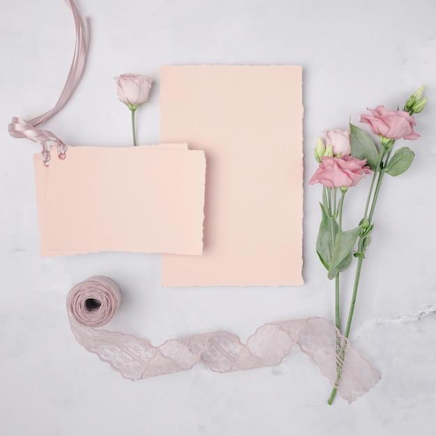 Plano hermoso arreglo con invitaciones de boda y flores. Foto gratis
