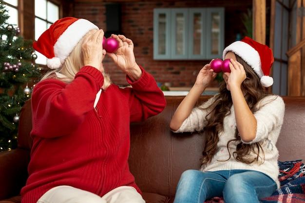 Plano medio abuela y niño jugando con bolas de navidad Foto gratis
