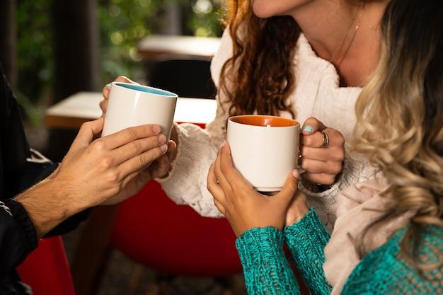 Plano medio de amigo con tazas de café Foto gratis
