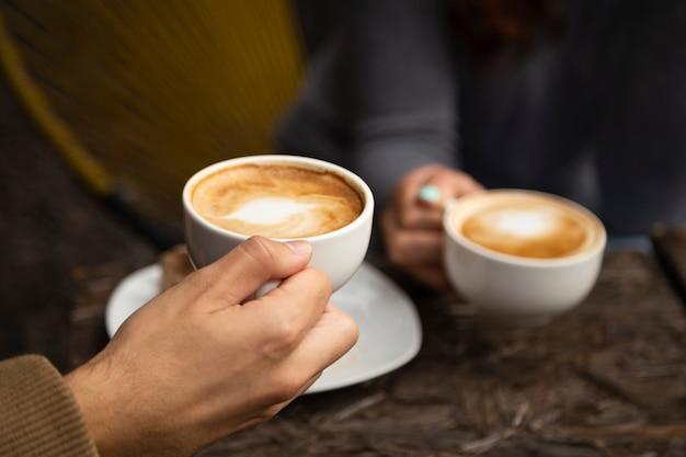 Plano medio de amigos tomando café juntos Foto gratis