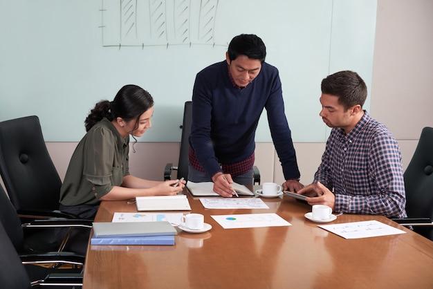 Plano medio del departamento financiero discutiendo la estrategia de desarrollo Foto gratis