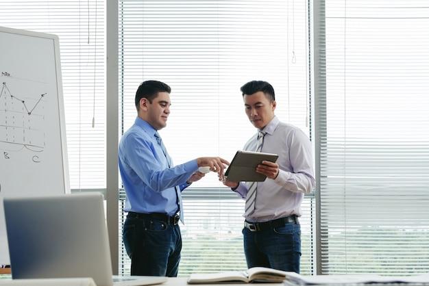 Plano medio de dos colegas de pie en la oficina y discutiendo datos en la tableta Foto gratis