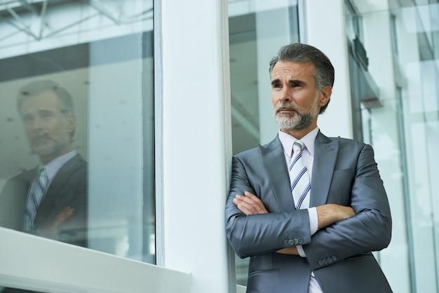 Plano medio del empresario de pie con los brazos cruzados apoyándose en el marco de la ventana Foto gratis