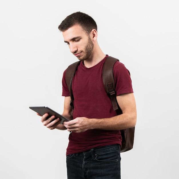 Plano medio del hombre mirando tableta Foto gratis