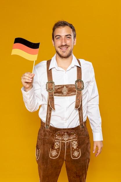 Plano medio del hombre que sostiene la bandera alemana Foto gratis