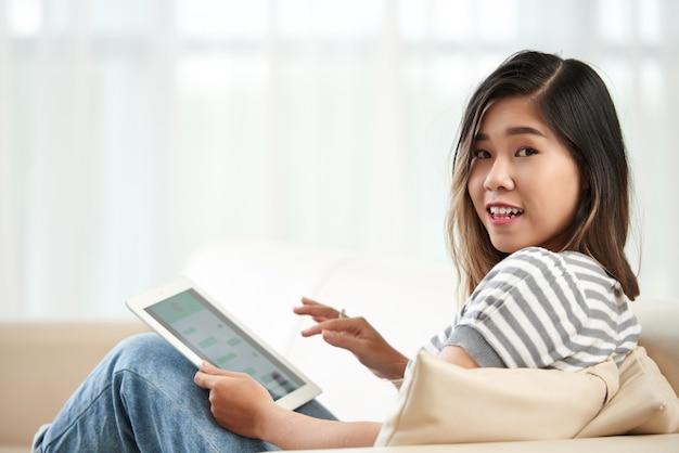 Plano medio de una joven asiática girando para mirar a la cámara distraída de su tablet pc Foto gratis