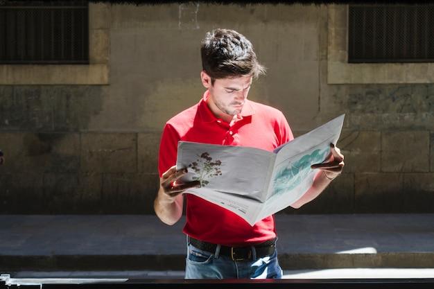 Plano medio de joven leyendo periódico en la calle Foto gratis